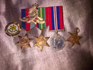 My grand fathers and fathers medals and cap badge